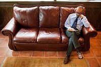 Mature Man Reading Book on Leather Sofa