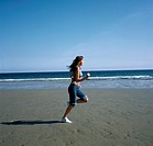 Teenage girl running along beach with her jeans rolled up UK.