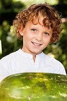 Close_up of smiling boy holding watermelon