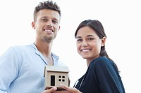 Portrait of a young couple holding a small model house
