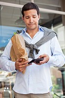 Mid adult man checking the empty wallet with paper bag full of vegetables (thumbnail)