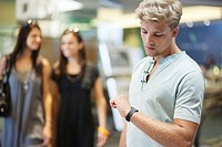 Young man checking the time with two women in the background at a clothing store