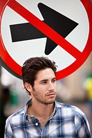 Handsome man thinking with no entry sign in the background