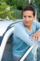 Mid adult man leaning at open car door (thumbnail)