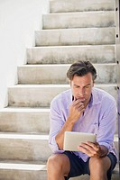 Mid adult man sitting on steps and using a digital tablet