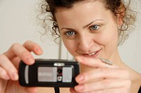 A woman taking a photo with a camera mobile phone.