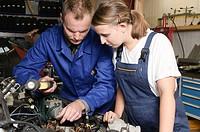 Der Meister erklärt der Auszubildenden die Arbeit am Motorraum in der Autowerkstatt