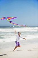 Mid adult man flying kite on the beach