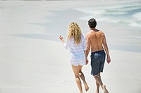 Rear view of a couple walking on the beach