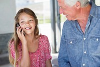 Girl talking on a mobile phone with her grandfather near her