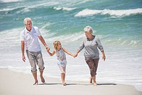 Senior couple walking with their granddaughter on the beach
