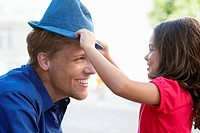 Cute little girl putting on a hat to her father