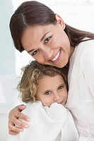Portrait of a woman hugging her daughter wrapped in towel