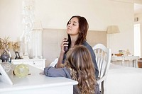 Young woman applying perfume while her daughter beside her