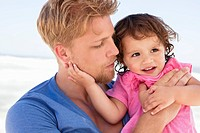 Close_up of a man carrying his daughter on the beach