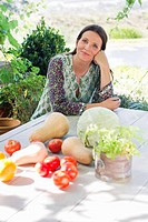 Portrait of a mature woman sitting and vegetables on table