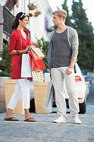 Young couple looking at each other with shopping bags on a street (thumbnail)