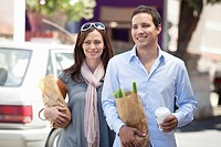 Smiling couple walking with paper bags full of vegetables
