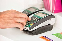 Sales clerk using a credit card reader at counter