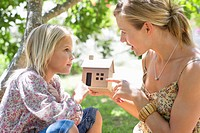 Little girl and her mother holding dollhouse outdoors
