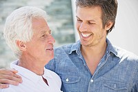 Close-up of a mid adult man smiling with his father (thumbnail)