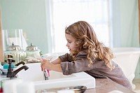 Cute little girl brushing teeth at bathroom sink