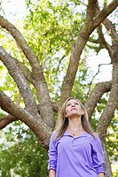 Low angle view of a young woman standing under a tree