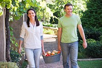 Mature couple carrying fruits basket in a garden