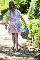 Rear view of a little girl watering to plants outdoors