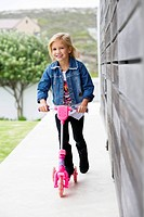 Portrait of a smiling girl riding a push scooter