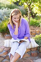 Beautiful young woman reading book in garden with hand on chin