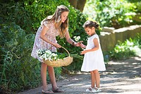 Girl giving flower to her little sister