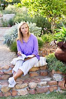 Contemplative young woman looking away in garden while holding book