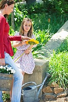 Cute little girl and mother holding sunflower outdoors