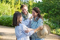Happy mature couple standing with their mother in a garden
