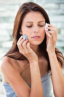 Close_up of a woman touching stones on her face