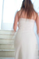 Blurry back view of a woman in a white dress walking up a stairway, indoors