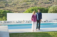 Mid adult couple standing at the poolside (thumbnail)