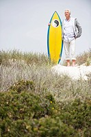 Senior man standing with surfboard on the beach (thumbnail)