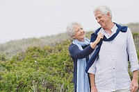 Senior woman putting sweater on husband's shoulder on the beach