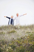 Senior couple pointing at different direction against clear sky