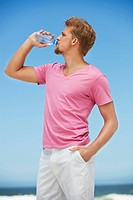 Young man drinking water from a water bottle on the beach