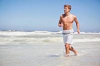 Man running shirtless on the beach