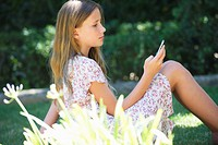 Cute little girl using a mobile phone outdoors (thumbnail)