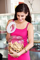 Smiling woman opening a jar of cookies in a bakery