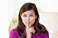 Portrait of a woman showing keep silence gesture (thumbnail)