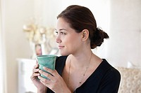 Young woman drinking tea at home