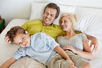 Parents with their son relaxing in bed