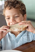 Close_up of a boy eating bread