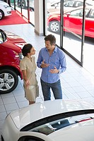 Female salesperson showing car to mid adult man in showroom